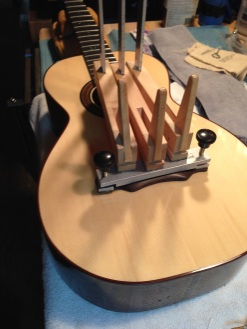 Bridge being attached with hide glue on parlor guitar by © Jay Rosenblatt