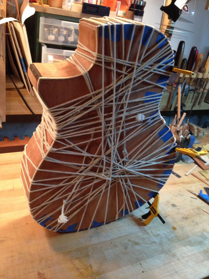 Roping curly maple binding in place on a Mahogany venetian cutaway acoustic guitar