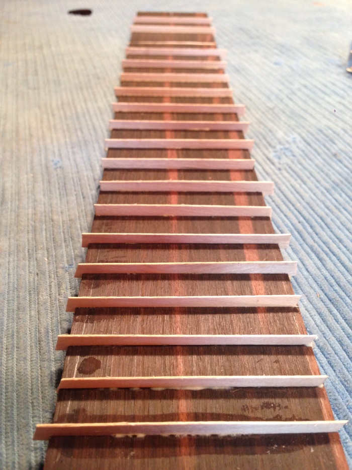 The fingerboard position markers are strips of maple inserted into the fret slots then sanded level