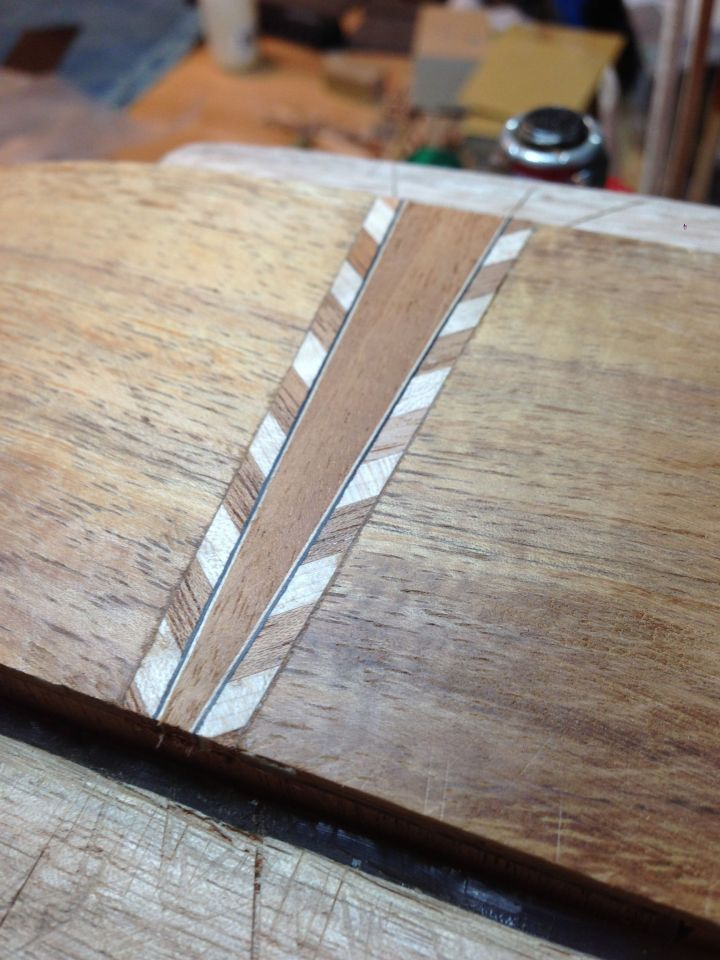 A simple end graft is constructed from mahogany and chevron binding and fit into a slot cut out in the tailpiece.