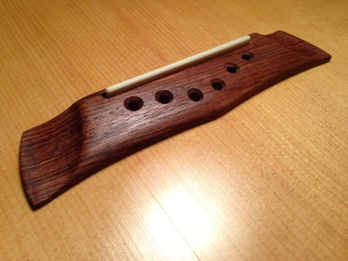 The bridge made from Honduran Rosewood. Carved to be similar to the original design, attached with hide glue.